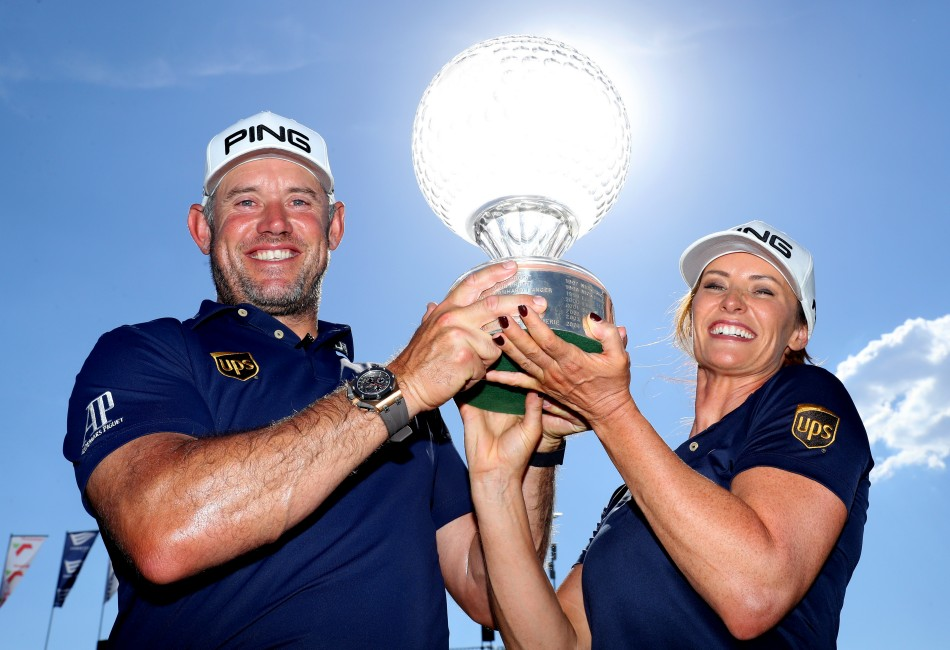 Lee Westwood and his partner and caddie, Helen Storey, lift the famous crystal trophy after his victory in the Nedbank Golf Challenge hosted by Gary Player.